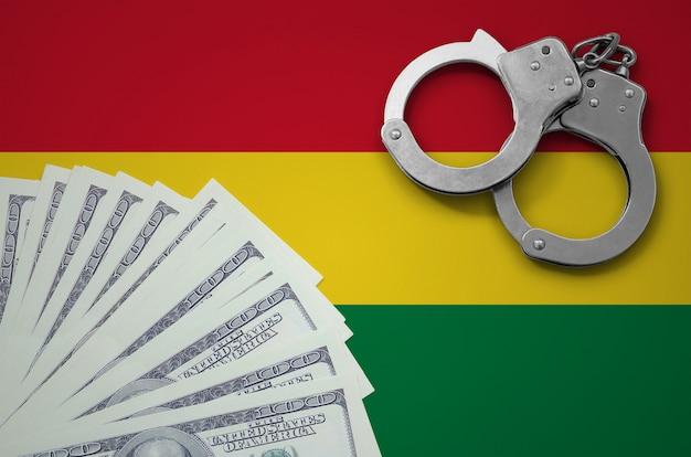 Vlag van bolivia met handboeien en een bundel dollars. het concept van illegale bankactiviteiten in amerikaanse valuta