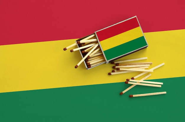Vlag van bolivia wordt weergegeven op een open luciferdoosje, waaruit verschillende wedstrijden vallen en op een grote vlag liggen