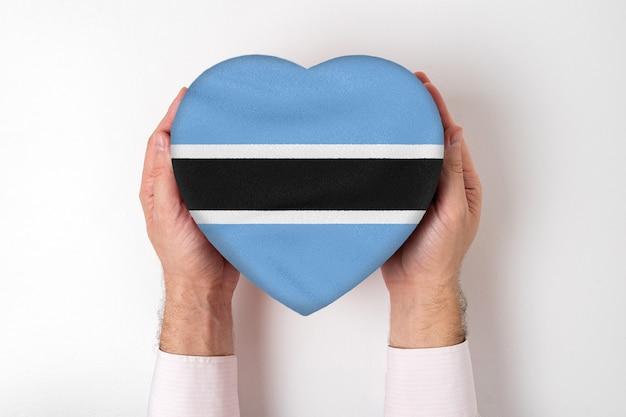 Vlag van botswana op een hartvormige doos in een mannelijke handen.