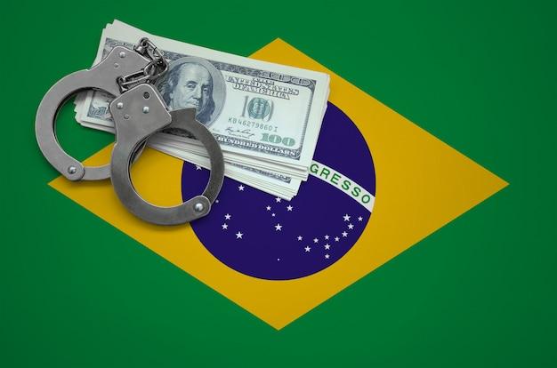 Vlag van brazilië met handboeien en een bundel dollars. het concept van het overtreden van de wet en dieven misdaden