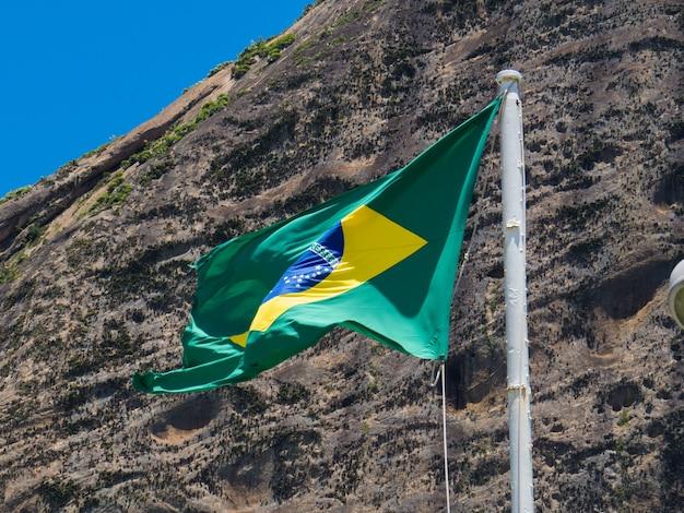 Vlag van brazilië wapperen in de wind voor de suikerbroodberg in rio de janeiro