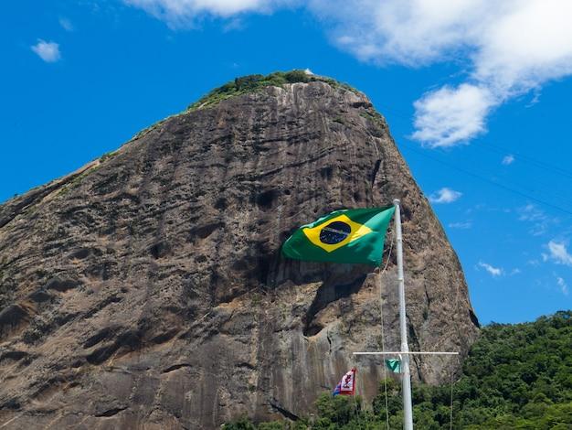 Vlag van brazilië wapperen op de achtergrond van de suikerbroodberg in rio de janeiro braziliaanse vlag