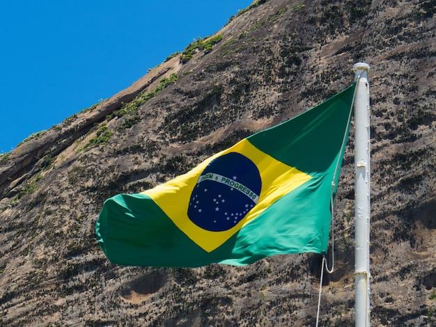 Vlag van brazilië wapperen voor de suikerbroodberg in rio de janeiro