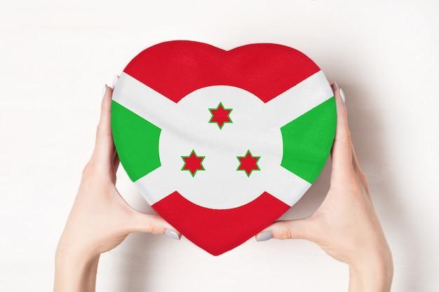 Vlag van burundi op een hartvormige doos in een vrouwelijke handen. witte achtergrond