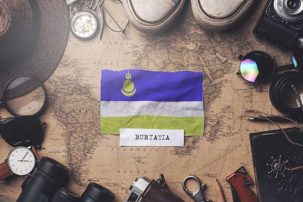 Vlag van buryatia tussen accessoires van de reiziger op oude vintage kaart. overhead schot
