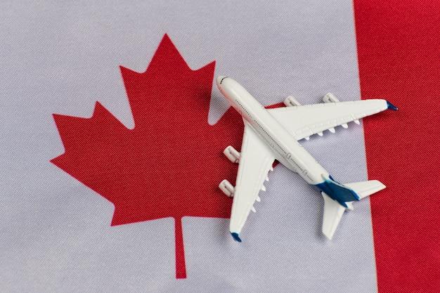 Vlag van canada en modelvliegtuig. vluchten naar canada na quarantaine. hervatting van vluchten