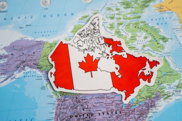 Vlag van canada op de achtergrond van de wereldkaart vlag op de achtergrond van de wereldkaart