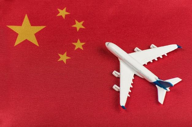 Vlag van china en modelvliegtuig. hervatting van vluchten na quarantaine, opening van grenzen