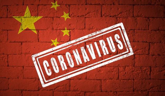 Vlag van china met originele verhoudingen. gestempeld met het coronavirus. bakstenen muur textuur. corona-virusconcept. op de rand van een covid-19- of 2019-ncov-pandemie.