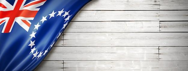 Vlag van de cookeilanden op oude witte muur. horizontale panoramische banner.