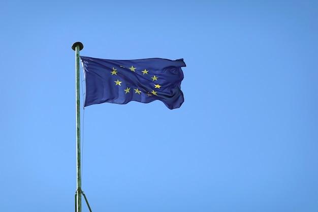 Vlag van de europese unie die op vlaggenmast op zonnige dag over duidelijke wolkenloze blauwe hemel golven