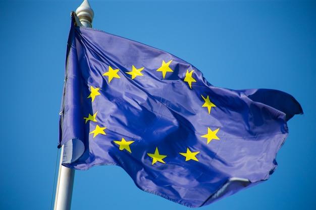 Vlag van de europese unie wapperen tegen blauwe hemel