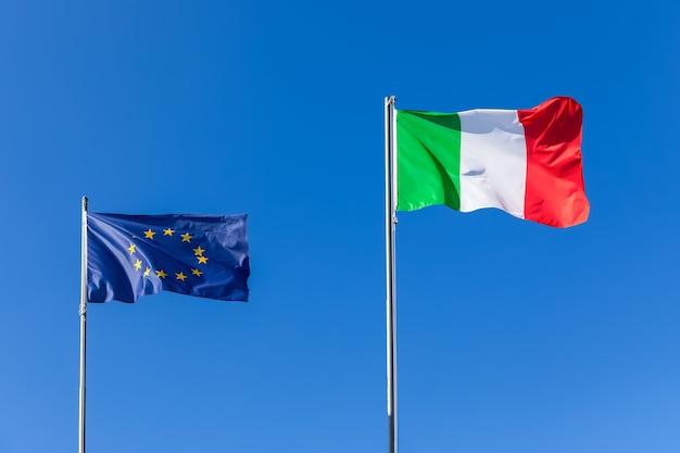 Vlag van de europese unione en de vlag van italië op de blauwe hemel