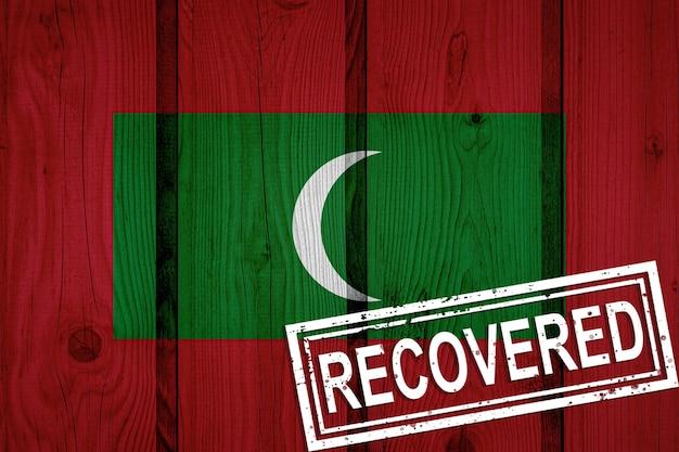 Vlag van de maldiven die de infecties van de corona-virusepidemie of het coronavirus hebben overleefd of hersteld. grunge vlag met stempel hersteld