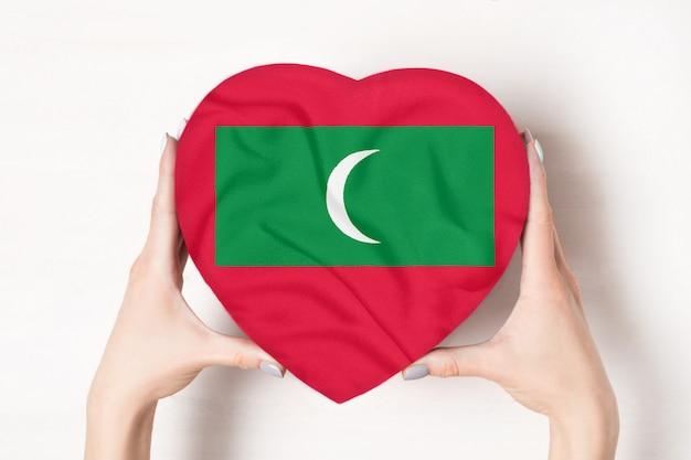 Vlag van de maldiven op een hartvormige doos in een vrouwelijke handen.