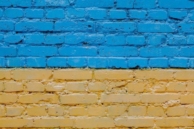 Vlag van de oekraïne geschilderd op oude bakstenen muur, achtergrond van geel-blauwe bakstenen muur