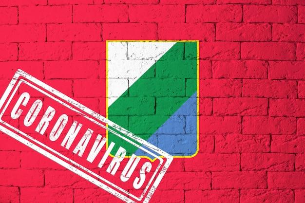 Vlag van de regio's van italië abruzzen met originele verhoudingen. gestempeld met het coronavirus. bakstenen muur textuur. corona-virusconcept. op de rand van een covid-19- of 2019-ncov-pandemie.