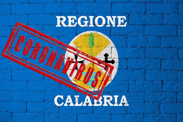 Vlag van de regio's van italië calabrië met originele verhoudingen. gestempeld met het coronavirus. bakstenen muur textuur. corona-virusconcept. op de rand van een covid-19- of 2019-ncov-pandemie.