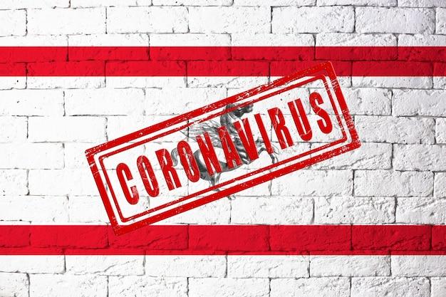 Vlag van de regio's van italië toscane met originele verhoudingen. gestempeld met het coronavirus. bakstenen muur textuur. corona-virusconcept. op de rand van een covid-19- of 2019-ncov-pandemie.