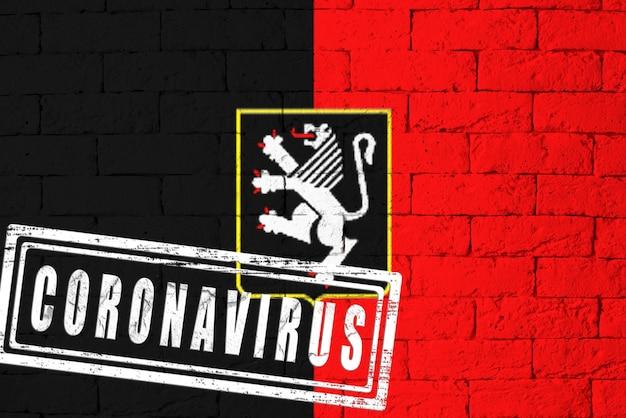 Vlag van de regio's van italië valle d'aosta met originele verhoudingen. gestempeld met het coronavirus. bakstenen muur textuur. corona-virusconcept. op de rand van een covid-19- of 2019-ncov-pandemie.