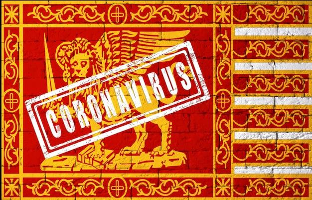 Vlag van de regio's van italië venetië met originele verhoudingen. gestempeld met het coronavirus. bakstenen muur textuur. corona-virusconcept. op de rand van een covid-19- of 2019-ncov-pandemie.