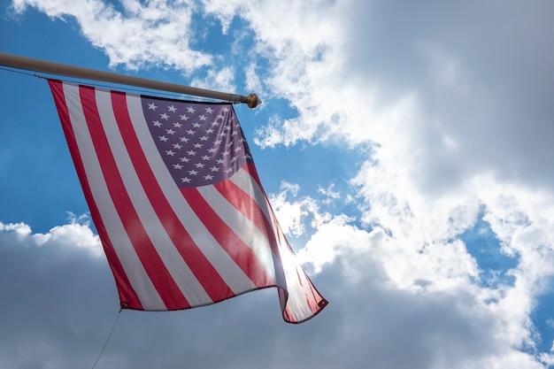 Vlag van de verenigde staten van amerika zwaaien in de blauwe lucht laag uitzicht op de amerikaanse vlag van de vs