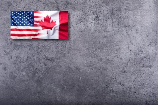 Vlag van de vs en de vlag van canada op concrete achtergrond.