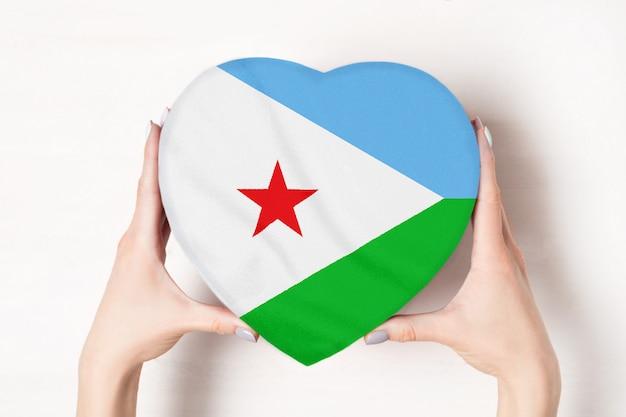 Vlag van djibouti op een hartvormige doos in een vrouwelijke handen.
