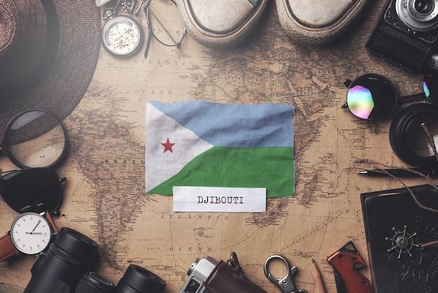 Vlag van djibouti tussen accessoires van de reiziger op oude vintage kaart. overhead schot