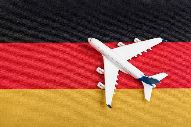 Vlag van duitsland en modelvliegtuig. hervatting van vluchten na quarantaine, opening van grenzen
