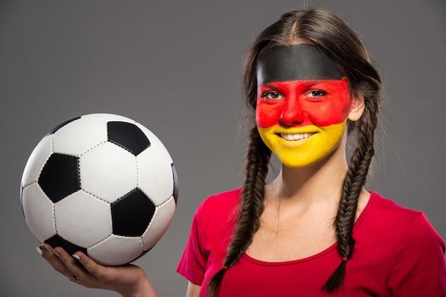 Vlag van duitsland geschilderd op een gezicht van een jonge vrouw.