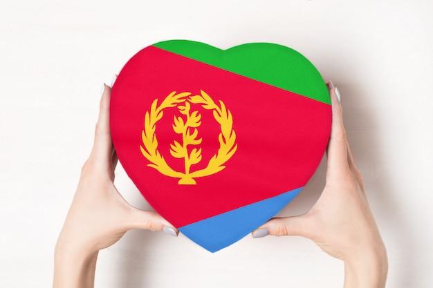 Vlag van eritrea op een hartvormige doos in een vrouwelijke handen.