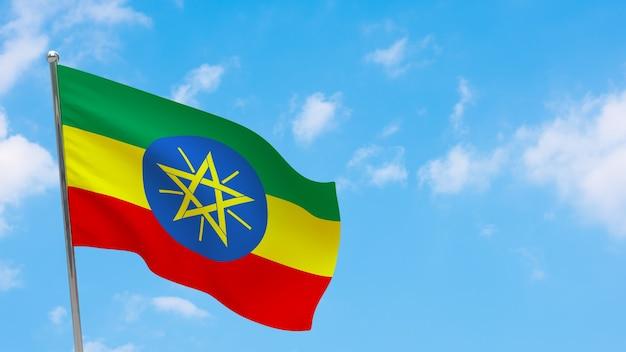 Vlag van ethiopië op paal. blauwe lucht. nationale vlag van ethiopië
