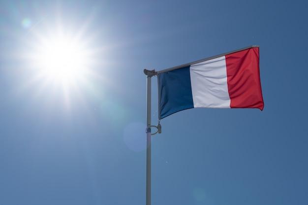 Vlag van frankrijk zwaaien over blauwe hemel en grote zon