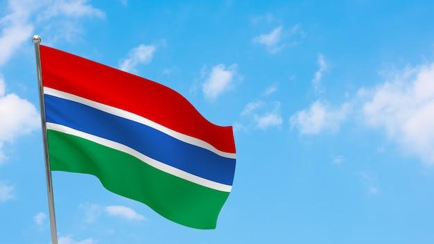 Vlag van gambia op paal. blauwe lucht. nationale vlag van gambia