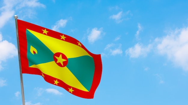 Vlag van grenada op paal. blauwe lucht. nationale vlag van grenada