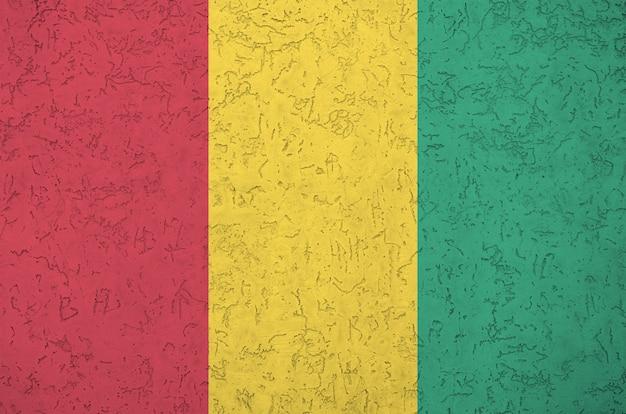 Vlag van guinee afgebeeld in heldere verfkleuren op oude reliëf pleistermuur.