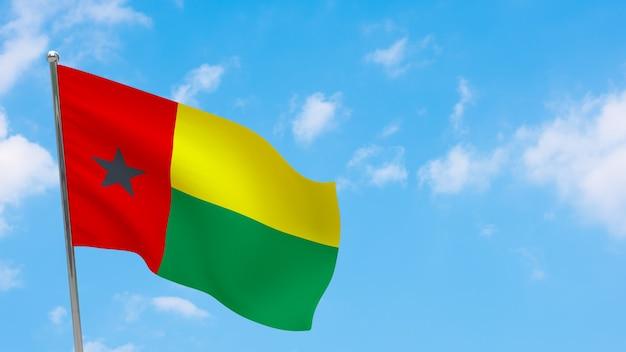 Vlag van guinee-bissau op paal. blauwe lucht. nationale vlag van guinee-bissau