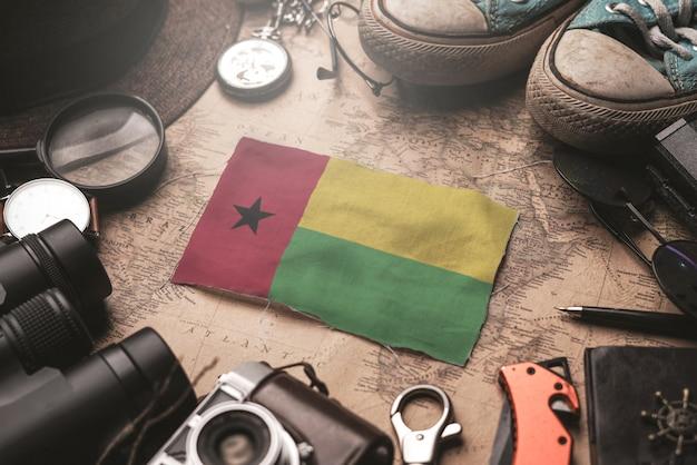 Vlag van guinee-bissau tussen de accessoires van de reiziger op oude vintage kaart. toeristische bestemming concept.