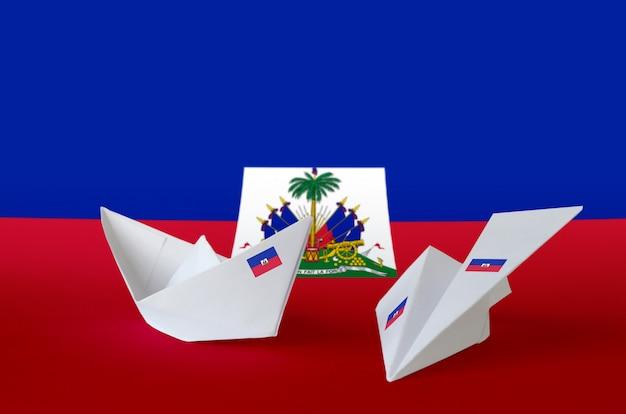 Vlag van haïti afgebeeld op papieren origami vliegtuig en boot. handgemaakt kunstconcept