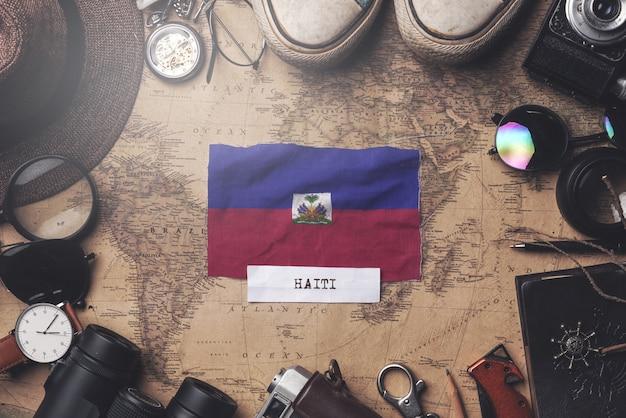 Vlag van haïti tussen accessoires van de reiziger op oude vintage kaart. overhead schot