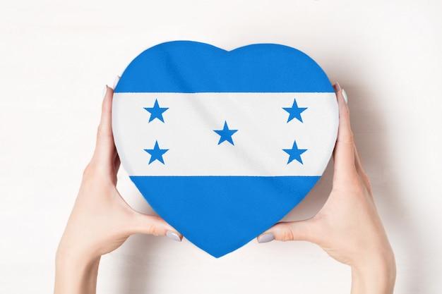 Vlag van honduras op een hartvormige doos in een vrouwelijke handen.