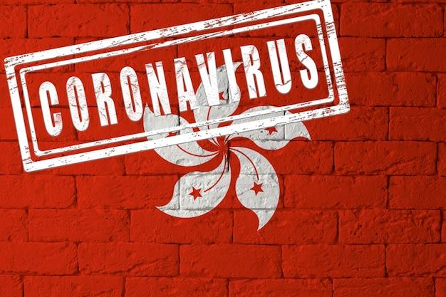 Vlag van hong kong met originele verhoudingen. gestempeld met het coronavirus. bakstenen muur textuur. corona-virusconcept. op de rand van een covid-19- of 2019-ncov-pandemie.