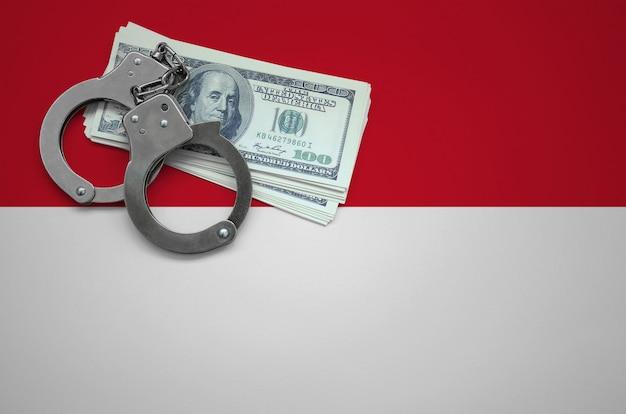 Vlag van indonesië met handboeien en een bundel dollars. het concept van het overtreden van de wet en dieven misdaden