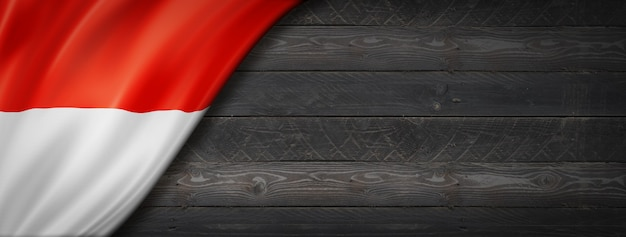 Vlag van indonesië op zwarte houten muur. horizontale panoramische banner.