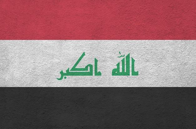 Vlag van irak afgebeeld in heldere verfkleuren op oude reliëf pleistermuur.