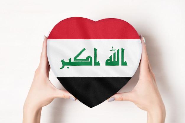 Vlag van irak op een hartvormige doos in een vrouwelijke handen