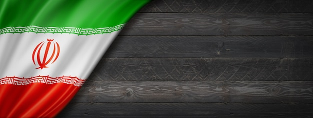Vlag van iran op zwarte houten muur. horizontale panoramische banner.