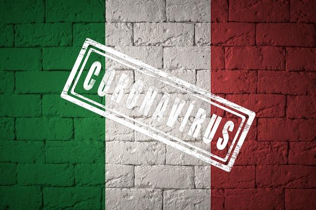 Vlag van italië met originele verhoudingen. gestempeld met het coronavirus. bakstenen muur textuur. corona-virusconcept. op de rand van een covid-19- of 2019-ncov-pandemie.
