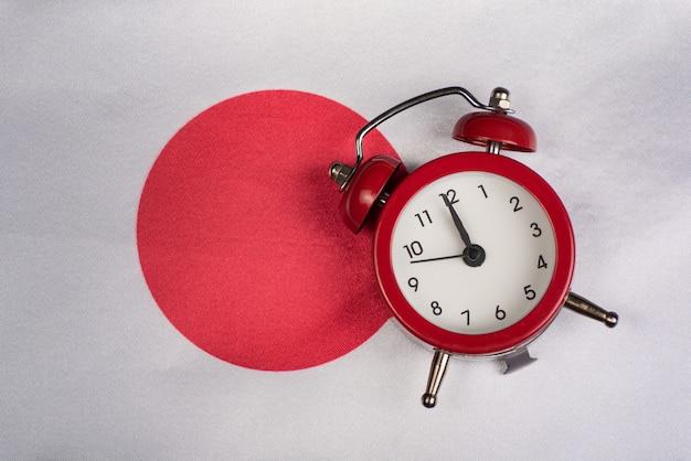 Vlag van japan en vintage wekker close-up. tijd om naar japan te reizen.